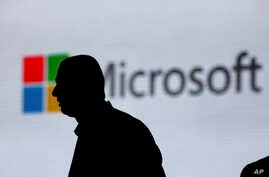 FILE - A man is silhouetted as he walks in front of a Microsoft logo at an event in New Delhi, India, Nov. 7, 2017. Microsoft says it's uncovered new Russian hacking attempts targeting U.S. political groups ahead of midterm elections in November.