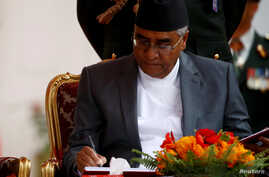 Newly elected Nepalese Prime Minister Sher Bahadur Deuba signs the oath after swearing-in ceremony  at the presidential building in Kathmandu, Nepal, June 7, 2017.