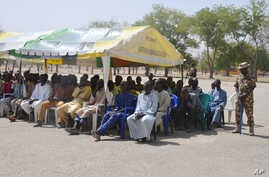 FILE- In this Feb. 12, 2016, file photo, men who were detained by Nigeria army who have no links to Boko Haram sit under a canopy before their release at the Giwa military barracks in Maiduguri, Nigeria.