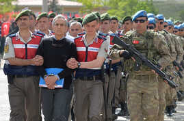 Akin Ozturk, a former Turkish Air Force commander who is accused of plotting and orchestrating last year's failed coup, is escorted by gendarmes as he arrives at the court in Ankara, Turkey, May 22, 2017.
