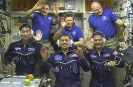 In this image taken from video from NASA, astronauts, front row from left, Kimiya Yui, of Japan, Oleg Kononenko, of Russia, and Kjell Lindgren, of the United States, wave after they boarded the International Space Station, early Thursday, July 23, 20