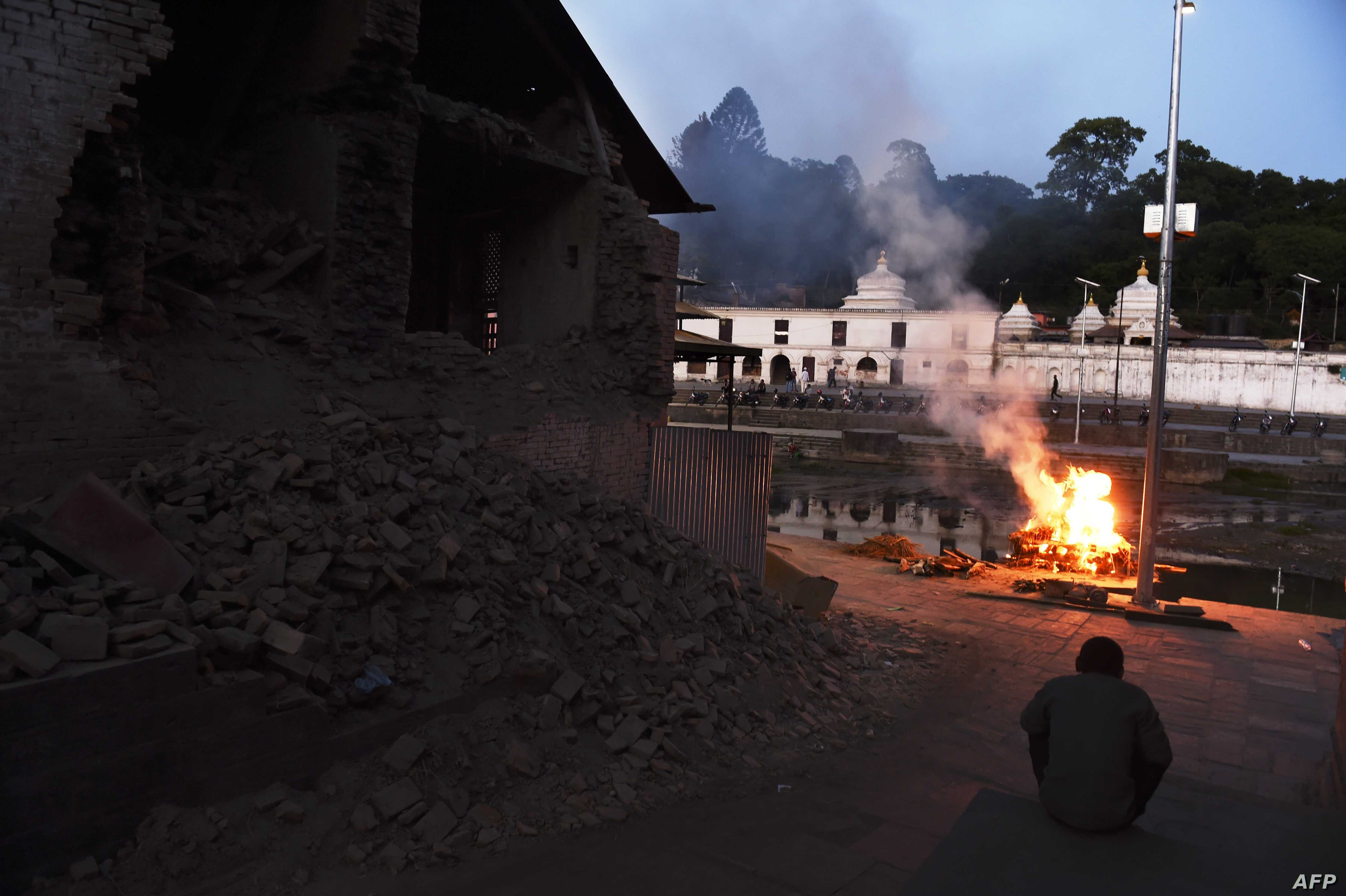 A Nepalese man sits near a collapsed wall and a burning pyre with the mortal remains of earthquake victim Sushila Thami at an open air crematorium in Kathmandu on May 5, 2015, after her body was brought from Dolakha.