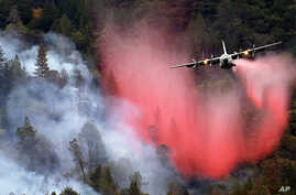 A firefighting plane drops a load of fire retardant over a smoldering hillside, Sept. 15, 2015, in Middletown, Calif.