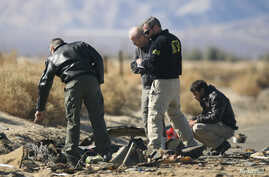 Investigators from the National Transportation Safety Board (NTSB) look at wreckage from the crash of Virgin Galactic's SpaceShipTwo near Cantil, California November 2, 2014. A suborbital passenger spaceship being developed by Richard Branson's Virgi