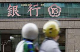 FILE - In this file photo from Jan. 16, 2007, motorcyclists pass by a branch of The Chinese Bank in Taipei, Taiwan.