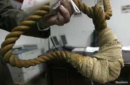 FILE - A museum worker shows a noose on display in a Iraqi museum in Baghdad, December 30, 2008.
