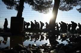The sun rises as refugees and migrants walk to pass from the northern Greek village of Idomeni to southern Macedonia, Friday, Sept. 11, 2015. The sudden onset of autumn has taken tens of thousands by surprise all along the Balkans route from Greece t...