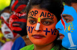 FILE - Students with their faces painted with messages pose during an HIV/AIDS awareness campaign to mark the International AIDS Candlelight Memorial, in Chandigarh, India, May 20, 2018.