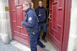 French police officers exit the residence of Kim Kardashian West in Paris Monday, Oct. 3, 2016.