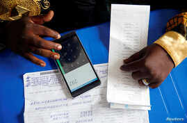 An official from Congo's Independent National Electoral Commission (CENI) uses his phone to calculate the numbers of presidential election votes at tallying center in Kinshasa, Democratic Republic of Congo, Jan. 4, 2019.