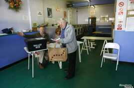 A man receives his voting paper from poll clerks in a public launderette being used as a polling station in Oxford, May 7, 2015.