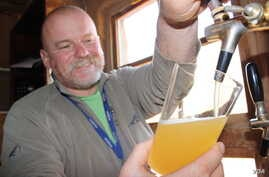 South African microbrewer Dirk Van Tonder pulls a pint of his Orange Blossom Weissbier, a German wheat beer. (Photo Credit: Darren Taylor)