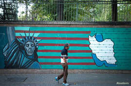 FILE - A man walks past an anti-U.S. mural in Tehran, Iran, Oct. 13, 2017.