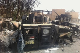Iraqi army armored vehicles are seen burned on a street of the northern city of Mosul, Iraq, Thursday, June 12, 2014.