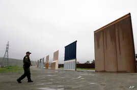 FILE - A Border Patrol agent walks towards prototypes for a border wall in San Diego, California, Feb. 5, 2019.