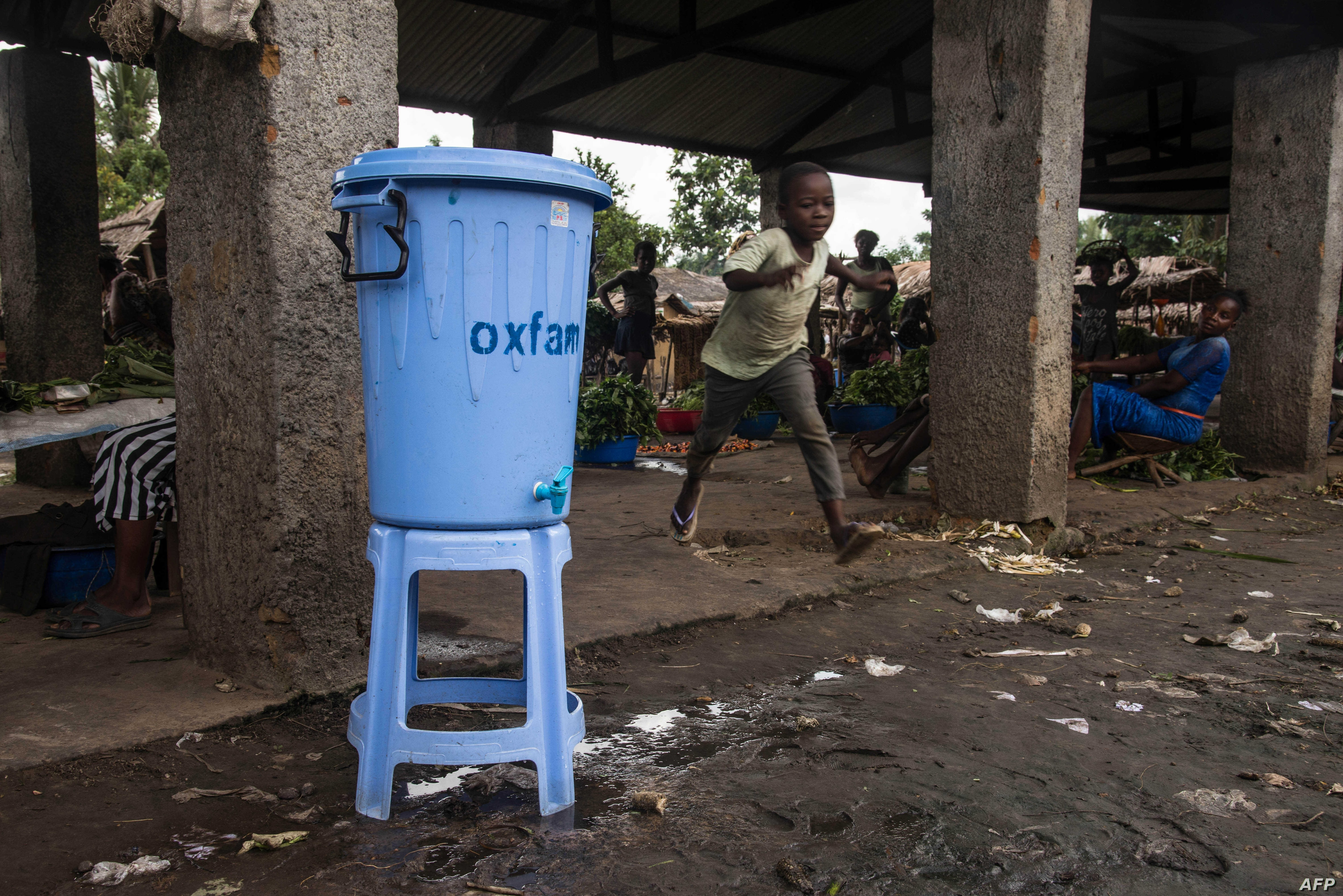 FILE - A boy runs past a dispenser containing water mixed with disinfectant, east of Mbandaka, DRC, May 23, 2018.