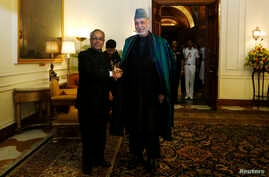 Afghanistan's President Hamid Karzai (R) shakes hands with his Indian counterpart Pranab Mukherjee ahead of their meeting at the presidential palace in New Delhi, India, May 21, 2013.