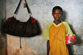 FILE - Harouna Ba, 11, a Talibe, or Islamic student, holds a begging bowl at a Dara, or Koranic school, in Pikine on the outskirts of Senegal's capital Dakar.