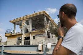 A man watches a house that was hit by a missile fired from Gaza Strip, in the city of Beersheba, southern Israel, Wednesday, Oct. 17, 2018. A medical service said a woman and her three children, whose home was struck, were being treated for shock aft