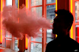 FILE - In this Feb. 20, 2014 file photo, a customer exhales vapor from an e-cigarette at a store in New York. A growing number of e-cigarette and vaporizer sellers have started offering college scholarships as a way to get their brands listed on univ