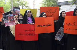 Holding anti-Saudi placards, Iranian university students attend a protest in front of the U.N. office in Tehran, Iran, April 16, 2015.