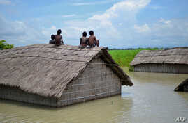 Indian children sit on the roof of a home submerged in flood waters in Batahidia on the Brahmaputra River in South Kamrup, southwest of Guwahati, July 27, 2016.