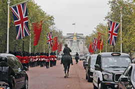 China's national flags are seen fixed on poles beside Union flags along The Mall near Buckingham Palace in London, Oct. 16, 2015, in anticipation of a state visit by Chinese President Xi Jinping and by his wife Peng Liyuan.