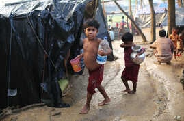 Rohingya children walk to their tents after fetching drinking water at a makeshift camp near Kutupalong refugee camp in Cox's Bazar, Bangladesh, Tuesday, Oct. 3, 2017. More than half a million Rohingya have fled from Myanmar to Bangladesh in just ove