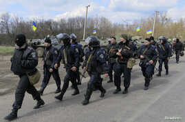 """Members of the Ukrainian Interior Ministry walk past armored personnel carriers at a checkpoint near the town of Izium, eastern Ukraine, April 15, 2014. Russia declared Ukraine on the brink of civil war on Tuesday as Kiev said an """"anti-terrorist oper"""