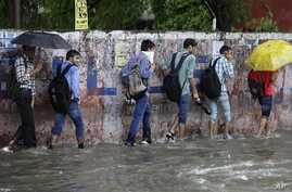 Indian boys wade through a flooded road as it rains in Jammu, India, Aug.16, 2014.