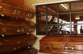 Coffins are displayed as a worker is reflected in a window at the Sizo funeral parlor in Soweto, South Africa, May 6, 2013.