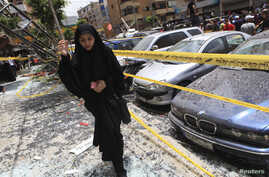 A woman walks over shattered glass, past damaged cars near the site of an explosion in Beirut's southern suburbs, Jul. 9, 2013.