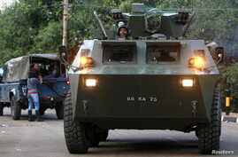 A Kenya Defence Forces (KDF) armoured military vehicle drives from the Westgate shopping centre after an exchange of gunfire inside the mall in Nairobi September 23, 2013. Thick smoke poured from the besieged Nairobi mall where Kenyan officials said