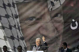 Palestinian president Mahmoud Abbas speaks during a rally marking the 6th anniversary of the death of his predecessor, Yasser Arafat, pictured in the background, in Ramallah, the West Bank, 11 Nov 2010