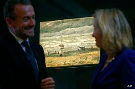 """Van Gogh Museum director Axel Rueger, left, and Jet Bussemaker, Minister for Education, Culture and Science, stand next to the stolen and recovered """"Seascape at Scheveningen"""" by Dutch master Vincent van Gogh, during a press conference in Amsterdam, N"""