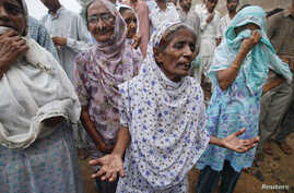 Women grieve and wait outside a building for their relatives after a fire at a garment factory in Karachi September 12, 2012.