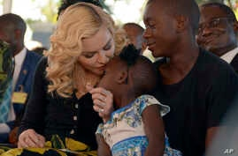 US musician Madonna, kisses one of her adopted daughters Stella, as son David Banda, right, looks on at the opening of The Mercy James Institute for Pediatric Surgery and Intensive Care, located at the Queen Elizabeth Central Hospital in the city of