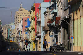 A man pushes his motorcycle as people walk on the freshly painted Reina Street on the route that Pope Francis will ride on his popemobile in Havana, Cuba, Sept. 19, 2015.