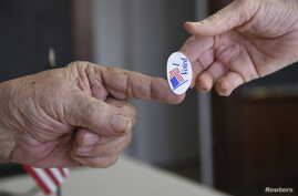 A poll worker hands a sticker to a voter on Super Tuesday in Stillwater, Oklahoma, March 1, 2016.