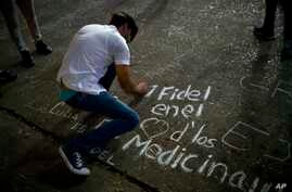 "A student writes on a sidewalk with chalk ""Fidel in the hearts of the med students"" during a vigil for the late Cuban leader Fidel Castro at the university where Castro studied law as a young man in Havana, Cuba, Nov. 26, 2016."