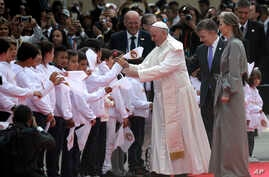 Colombia's President Juan Manuel Santos, second from right, and his wife Maria Clemencia Rodriguez accompany Pope Francis who is greeted by children upon his arrival to El Dorado airport in Bogota, Colombia, Sept. 6, 2017.