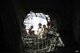 FILE - Boys look through a hole made by a Saudi-led airstrike on a bridge in Sana'a, Yemen, March 23, 2016.