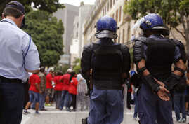 FILE - South African police provide security as Parliament workers, rear,  protest against low wages in Cape Town, South Africa, Nov. 11, 2015.