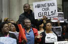 Demonstrators hold banners as they protest about the kidnapping of girls in Nigeria, near the Nigerian High Commission in London, May 9, 2014.