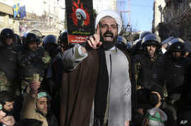 Surrounded by policemen, a Muslim cleric addresses a crowd during a demonstration to protest the execution of Saudi Shiite Sheikh Nimr al-Nimr, shown in the poster in background, in front of the Saudi embassy in Tehran, Iran, Sunday, Jan. 3, 2016.
