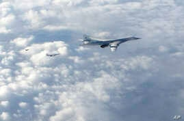 In this image made available by the Royal Air Force, Jan. 15, 2018, two Russian Blackjack Tupolev Tu-160 long-range bombers are followed by an RAF Typhoon aircraft (L) scrambled from RAF Lossiemouth, Scotland.
