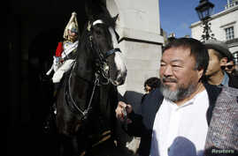 Artist Ai Weiwei passes a member of the Household Cavalry on duty outside Horse Guards Parade as he walks through central London, Sept. 17, 2015.