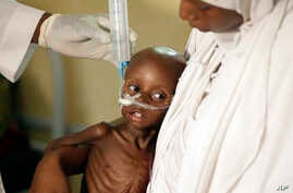 FILE - A doctor feeds a malnourished child at a feeding centre run by Doctors Without Borders in Maiduguri, Nigeria, Aug. 29, 2016.