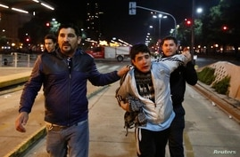 Undercover police officers detain a man after riot police fired tear gas and used water cannons to restrain a group of youths who hurled rocks and vandalized store fronts at a rally to celebrate Argentina's gutsy performance in a 1-0 loss to Germany.