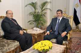 In this photo released by the Egyptian Presidency, President Mohammed Morsi, right, poses for a photograph with his new Prosecutor General, Talaat Abdullah, left, in Cairo, Egypt, Thursday, Nov. 22, 2012.